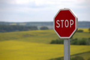 A red stop sign with countryside in the background