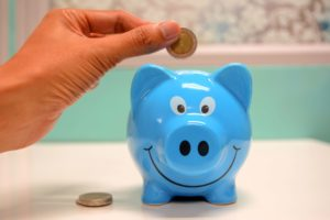 Hand putting coin in a piggy bank