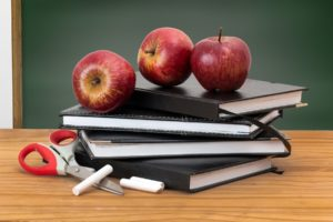 Pile of books with three apples on top and chalk and scissors next to