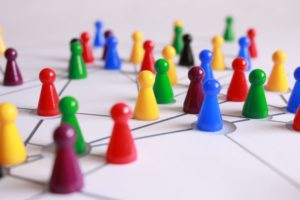 close up photo of differnt coloured game pieces on a white board.
