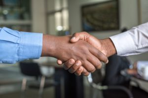 Two people shaking hands across the picture.